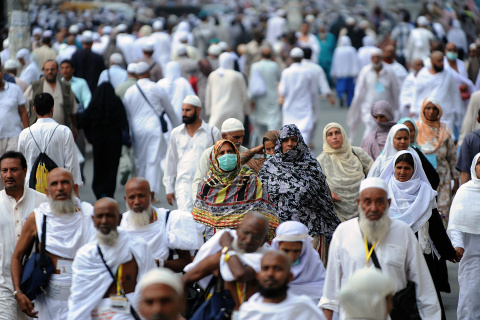 A Muslim pilgrim wears a mask as she walks to Mecca's Grand Mosque to perform evening prayers on October 8, 2013 prior to the start of the annual hajj pilgrimage which begins on October 13. More than two million Muslims have arrived in the holy city for the hajj, one of the world's largest human assemblies, amid concerns over the deadly MERS coronavirus. AFP PHOTO/FAYEZ NURELDINE (Photo credit should read FAYEZ NURELDINE/AFP/Getty Images)